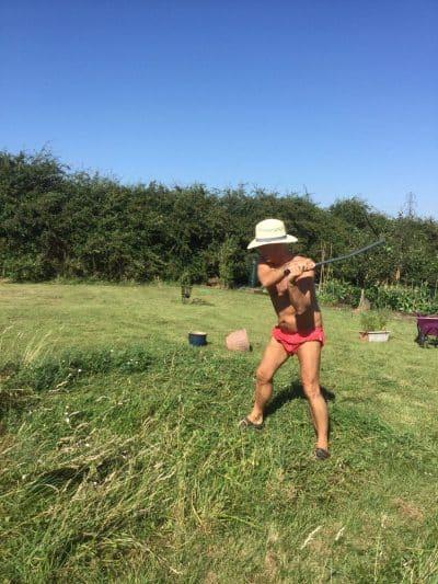 Man with scythe in garden